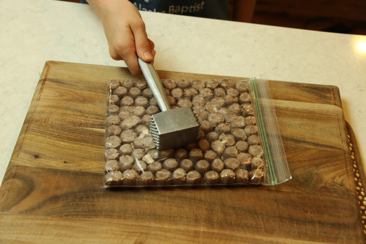 Crushing malted milk balls with meat tenderizer to use in malted milk cookies.