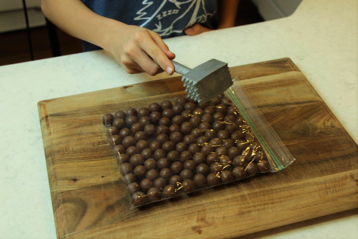 Crushing malted milk balls with meat tenderizer.