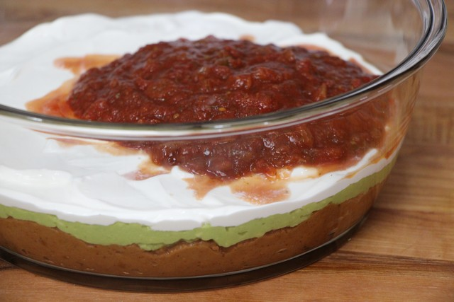 Adding sour cream and salsa to six layer guacamole dip