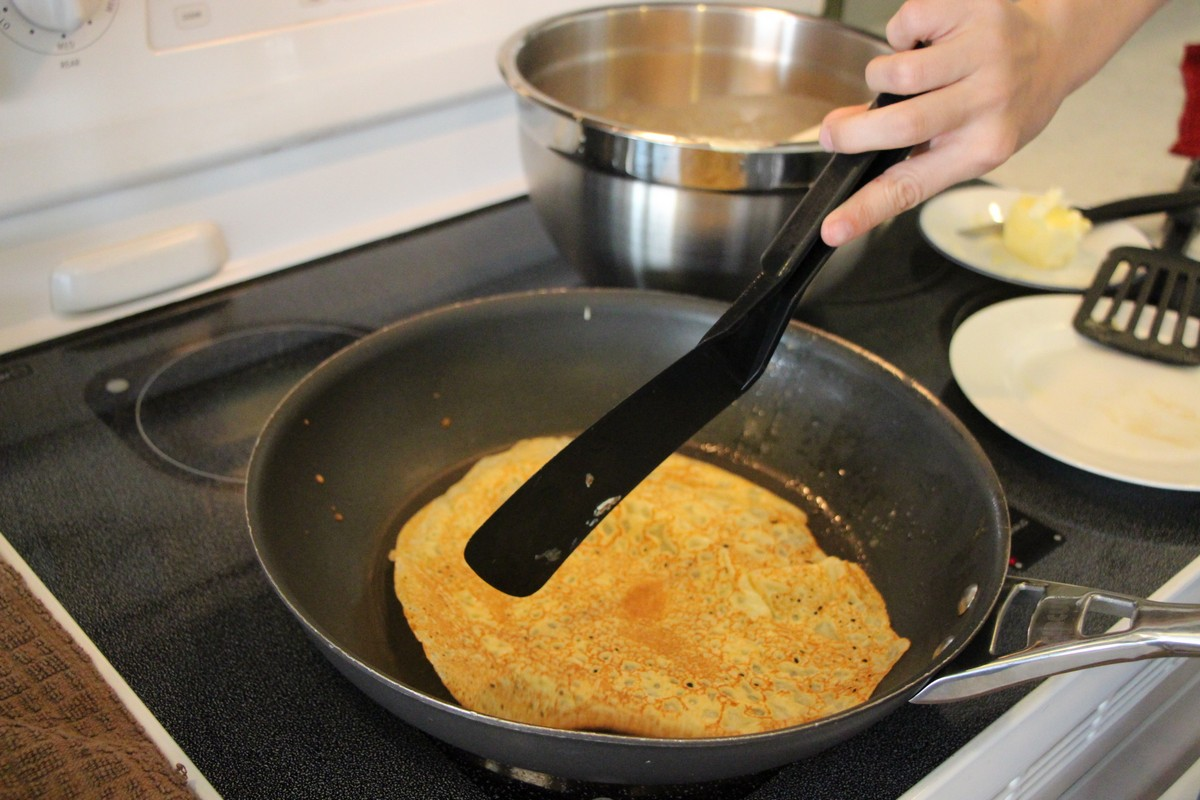 Making thin, authentic Norwegian pancakes, flipping over