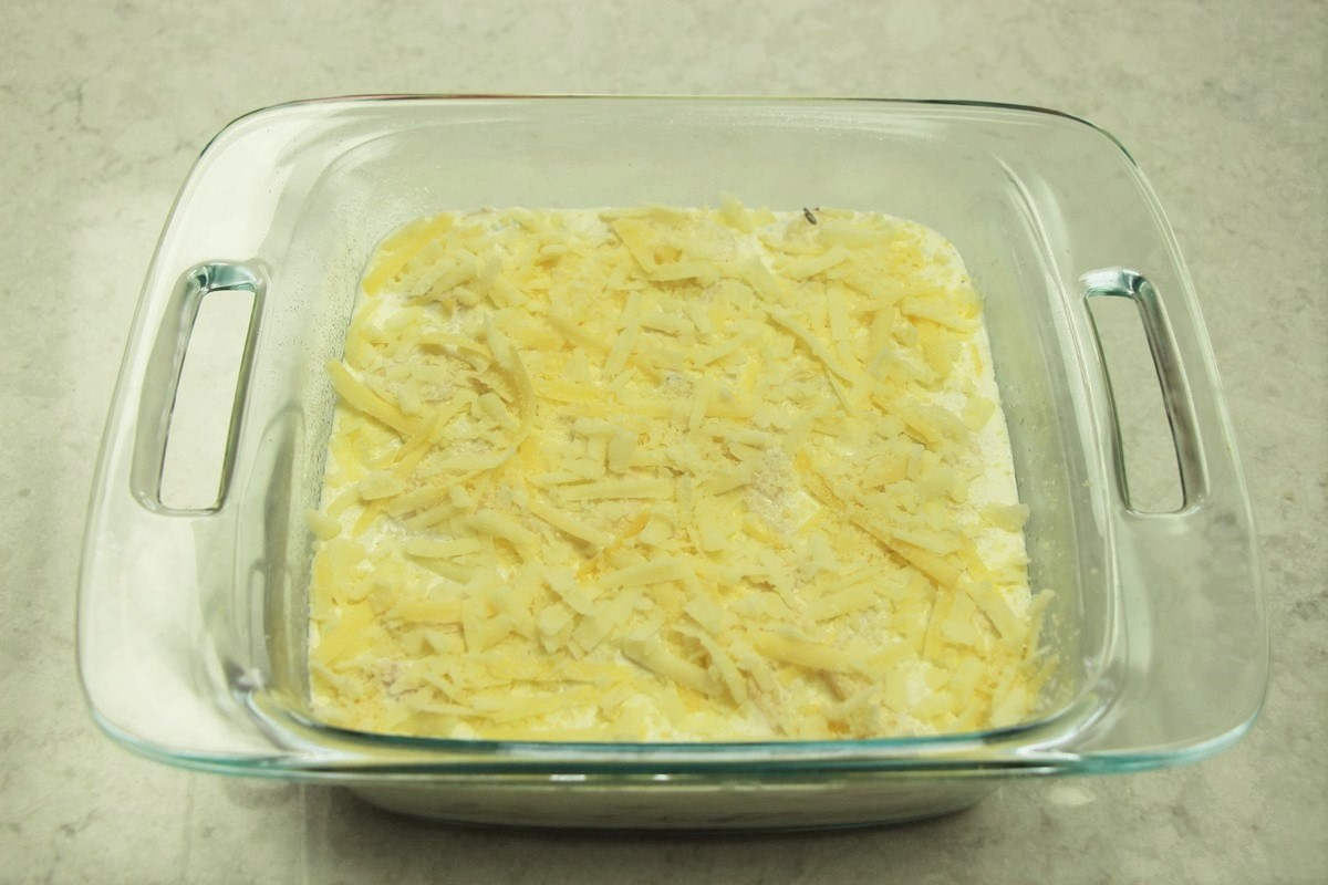 Layering cheese on deluxe scalloped potatoes