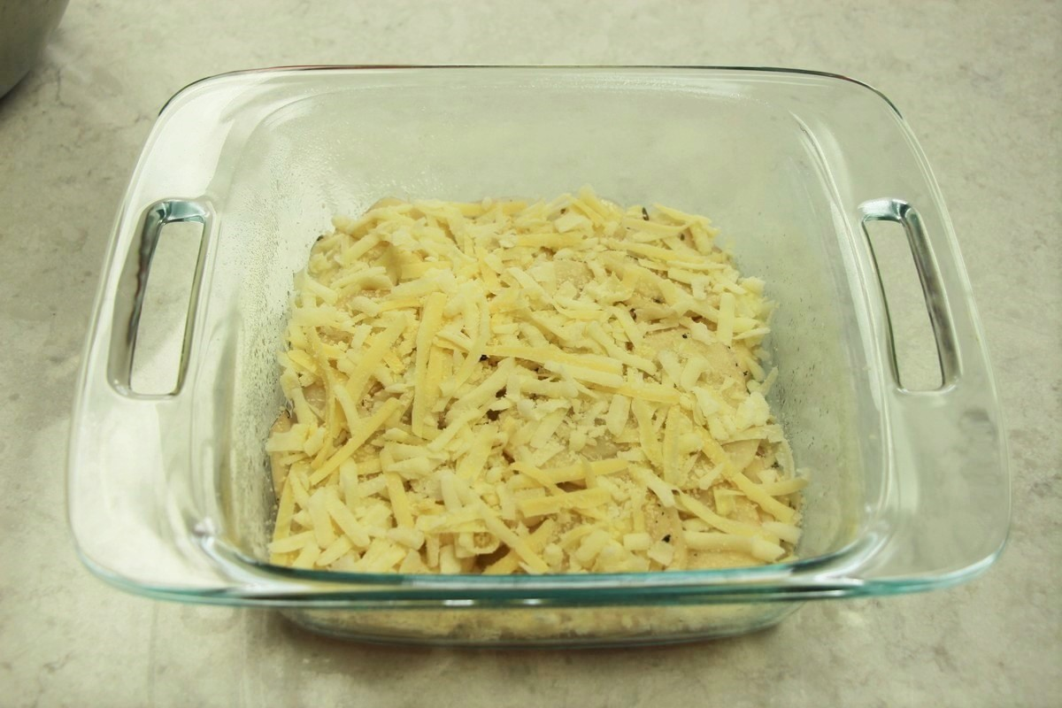 Layering cheese on sliced potatoes, for scalloped potato recipe