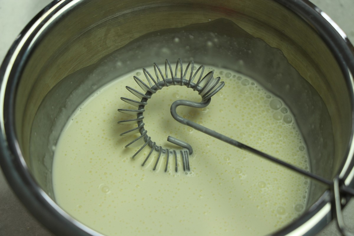 Using a flat whisk to whisk together heavy cream and sour cream