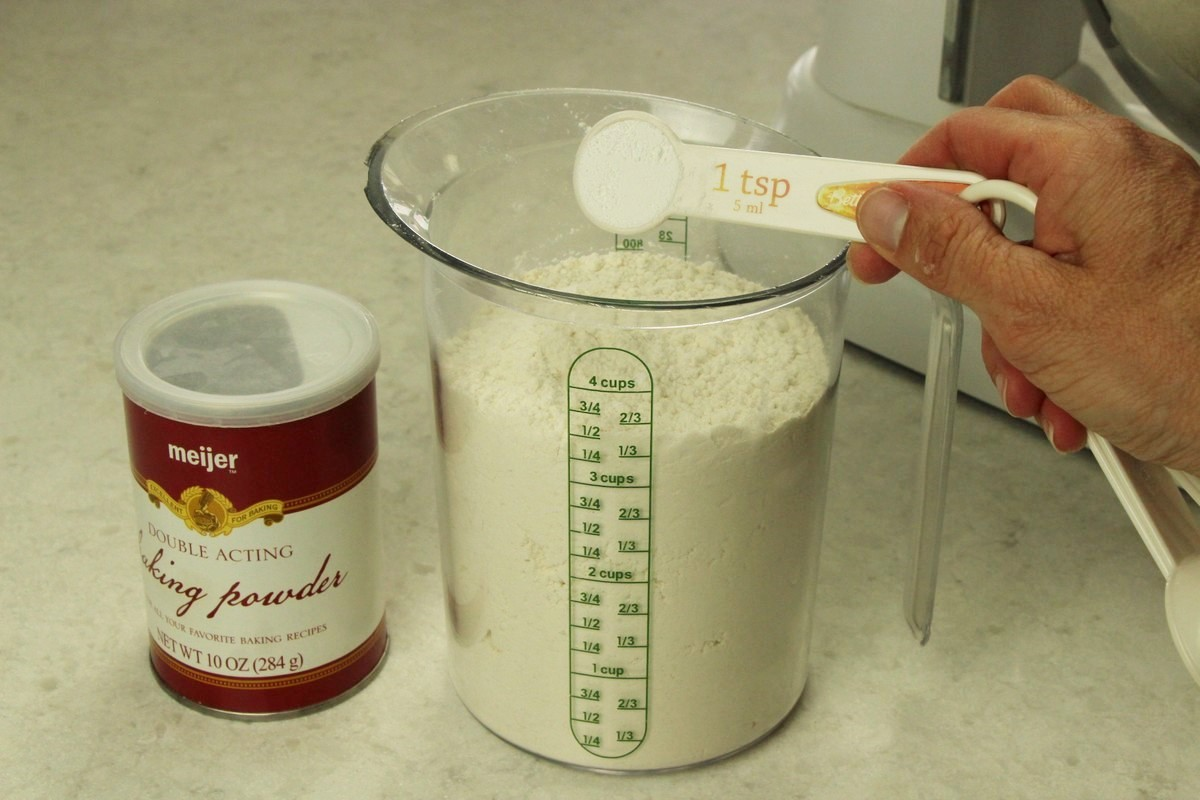 Measuring flour and baking powder for sugar cookie recipe.