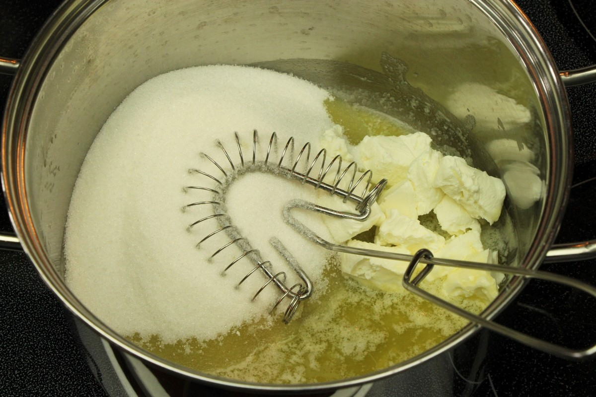 Mixing melted butter, sugar, and cream cheese for chewy sugar cookies